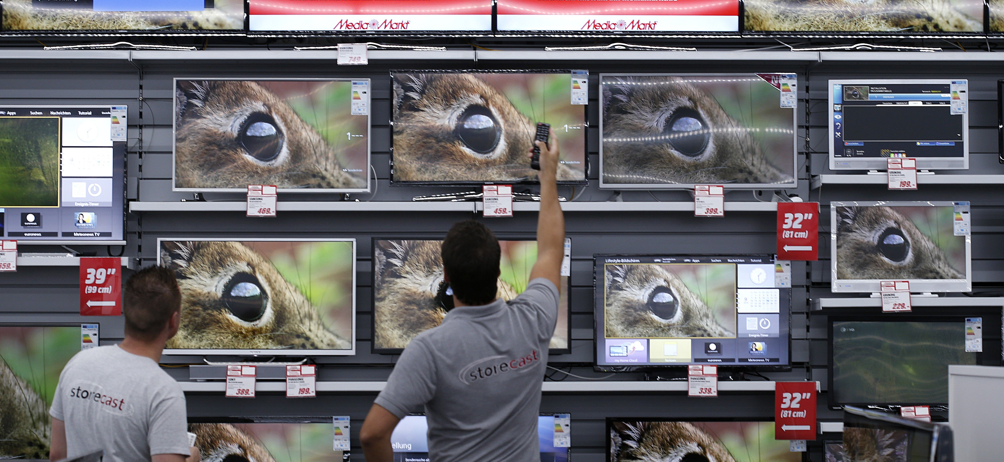 Employees of German electronics retailer Media-Saturn switch on television in their European state-of-the-art store in Ingolstadt, southern Germany, September 18, 2014. The shop will open in Ingolstadt on September 23.     REUTERS/Michaela Rehle (GERMANY - Tags: BUSINESS) - RTR46QP4