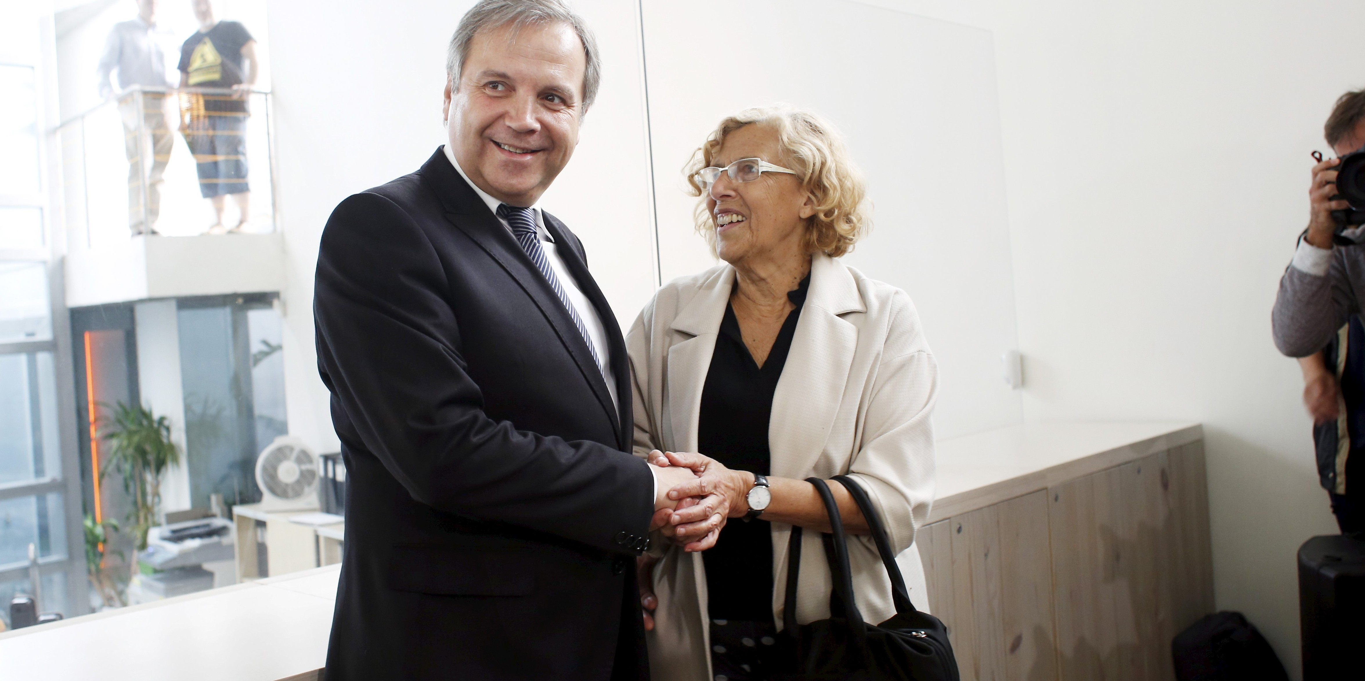 Ahora Madrid (Now Madrid) local candidate Manuela Carmena (C) and Socialist Party (PSOE) local candidate Antonio Miguel Carmona (L) hold hands as they pose at the start of a news conference in Madrid, Spain, June 12, 2015. Manuela Carmena, 71, cut a deal with the opposition Socialists to form a coalition administration. The left-wing former judge, backed by anti-austerity party Podemos, was named mayor of Spain's capital on Friday, ending 24 years of centre-right Popular Party (PP) rule in Madrid and delivering a setback to Prime Minister Mariano Rajoy. REUTERS/Susana Vera - RTX1G7QP