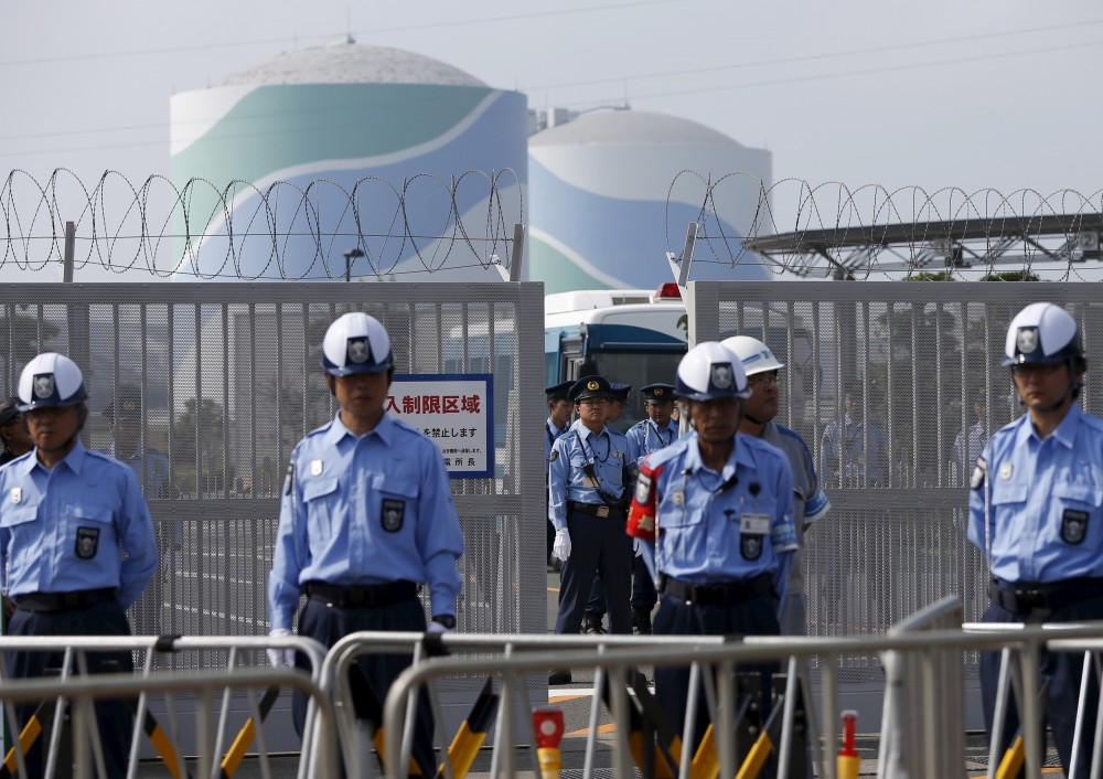 Police officers and security personnel stand guard at an entrance of Kyushu Electric Power's Sendai nuclear power station, during a protest demanding for the stop of the plant's restart, in Satsumasendai, Kagoshima prefecture, Japan August 9, 2015. Japan switched on a nuclear reactor for the first time in nearly two years on Tuesday, as Prime Minister Shinzo Abe seeks to reassure a nervous public that tougher standards mean the sector is now safe after the Fukushima disaster in 2011. The No.1 (L) and No.2 reactor buildings are seen in the background. Picture taken August 9, 2015. REUTERS/Issei Kato - RTX1NTTZ