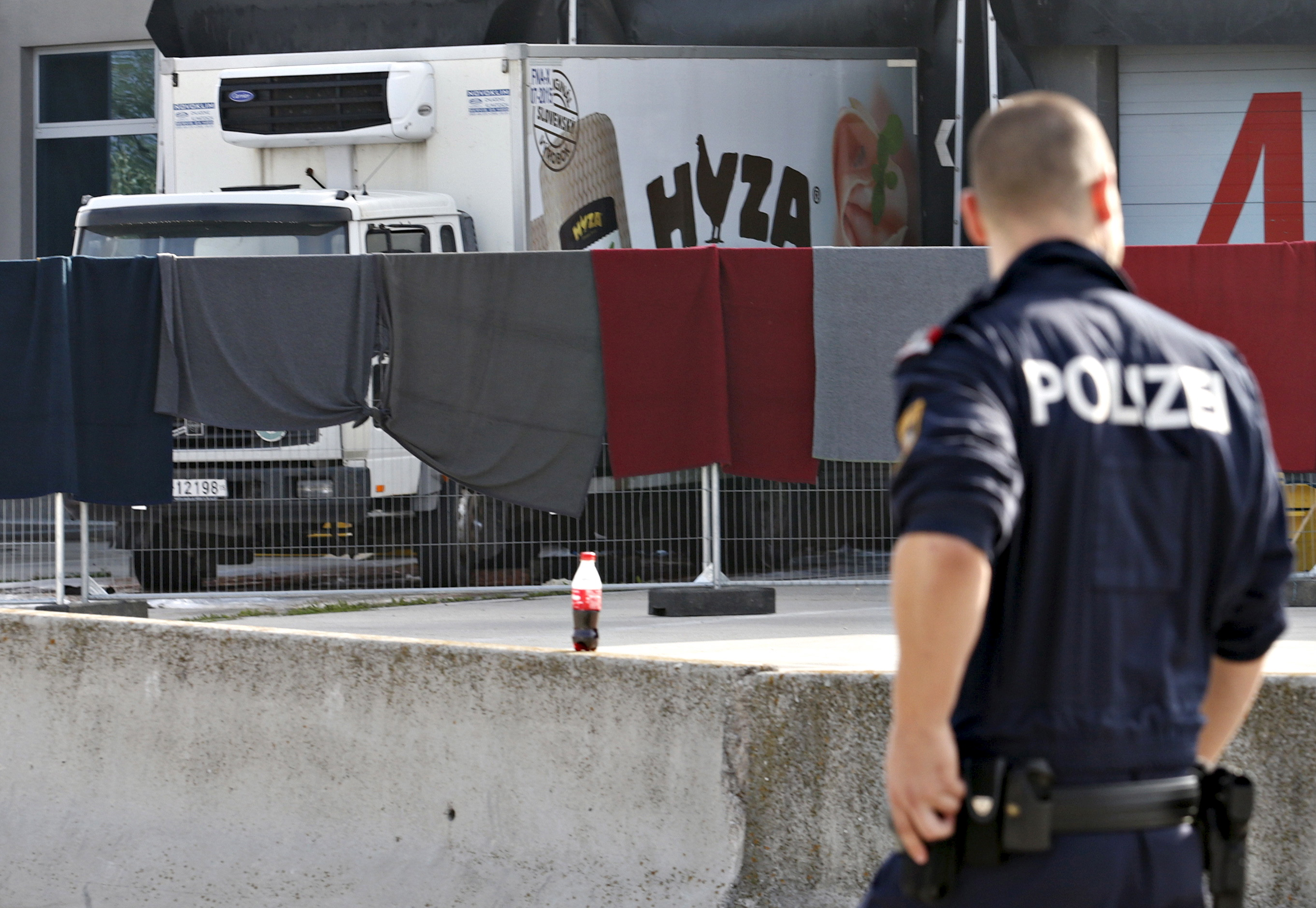A police officer walks by a truck discovered abandoned on an Austrian motorway containing more than 70 bodies as it sits at a customs building with refrigeration facilities in the village of Nickelsdorf, Austria, August 28, 2015. The abandoned refrigerated lorry was found by an Austrian motorway patrol near the Hungarian border, with fluids from the decomposing bodies seeping from its back door. REUTERS/Heinz-Peter Bader - RTX1PZP3