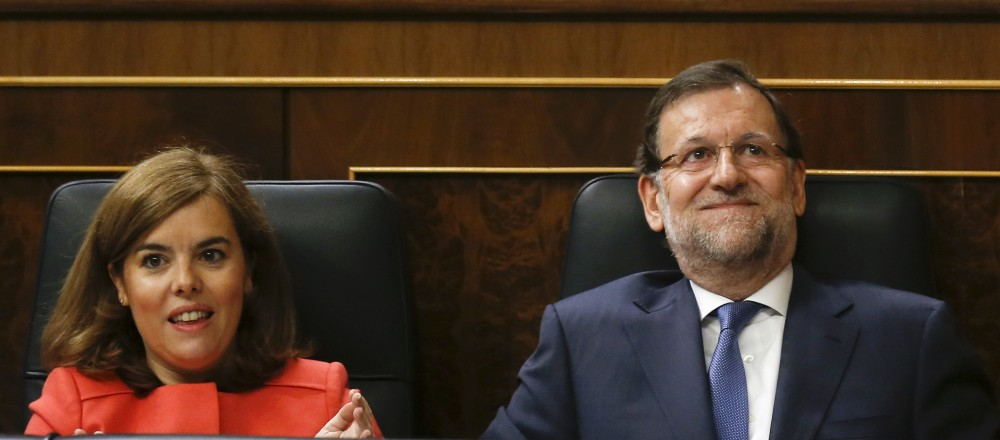 Spain's Prime Minister Mariano Rajoy (R) reacts, next to Deputy Prime Minister Soraya Saenz de Santamaria, to applause by party members after answering a question during a government control session at Spain's Parliament in Madrid, Spain, June 17, 2015. REUTERS/Andrea Comas - RTX1GUOM