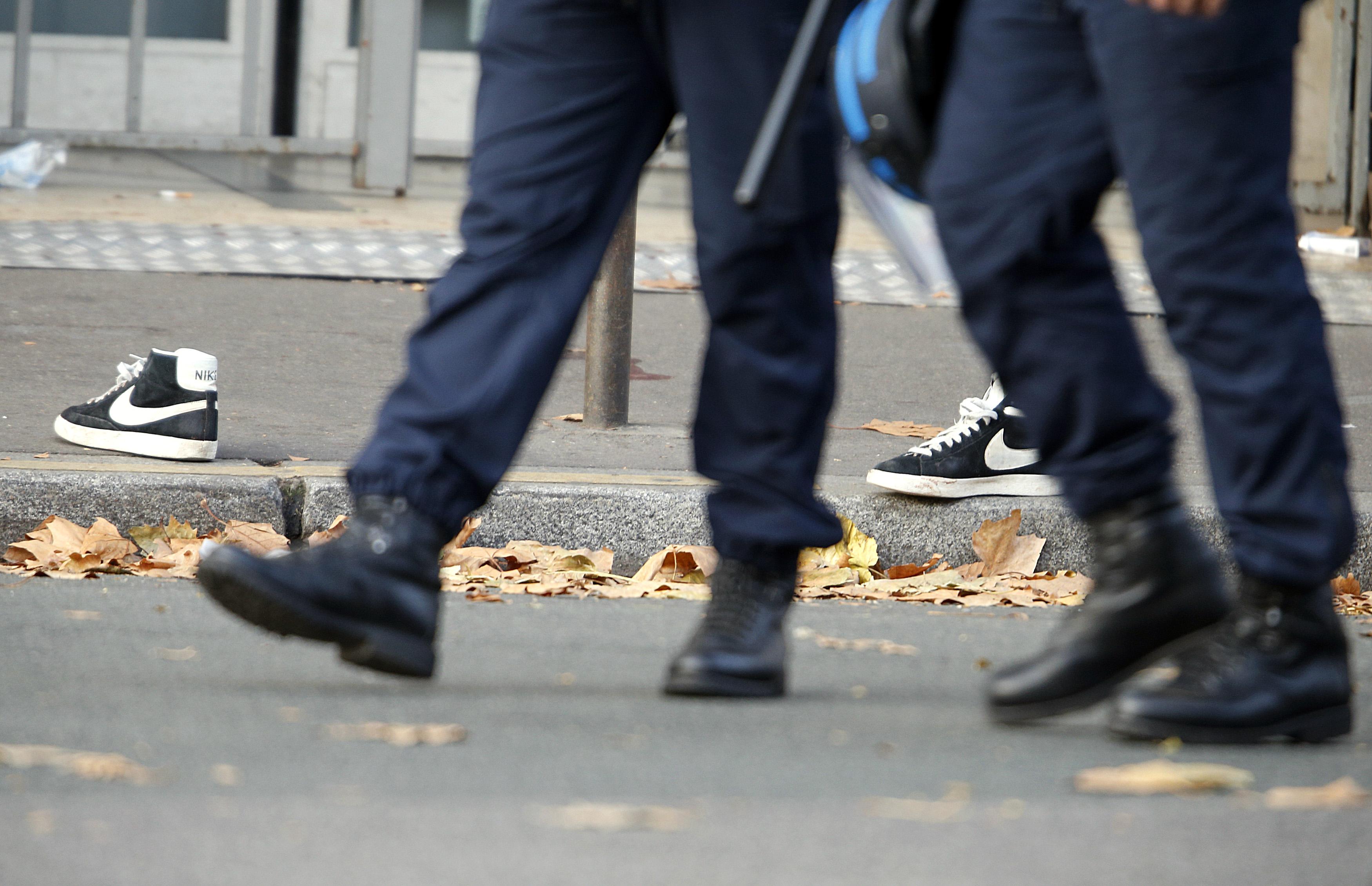 La POlicía pasa al lado de un par de zapatillas abandonadas en una de las zonas de los ataques de París.      REUTERS/Charles Platiau - RTS6Y5C