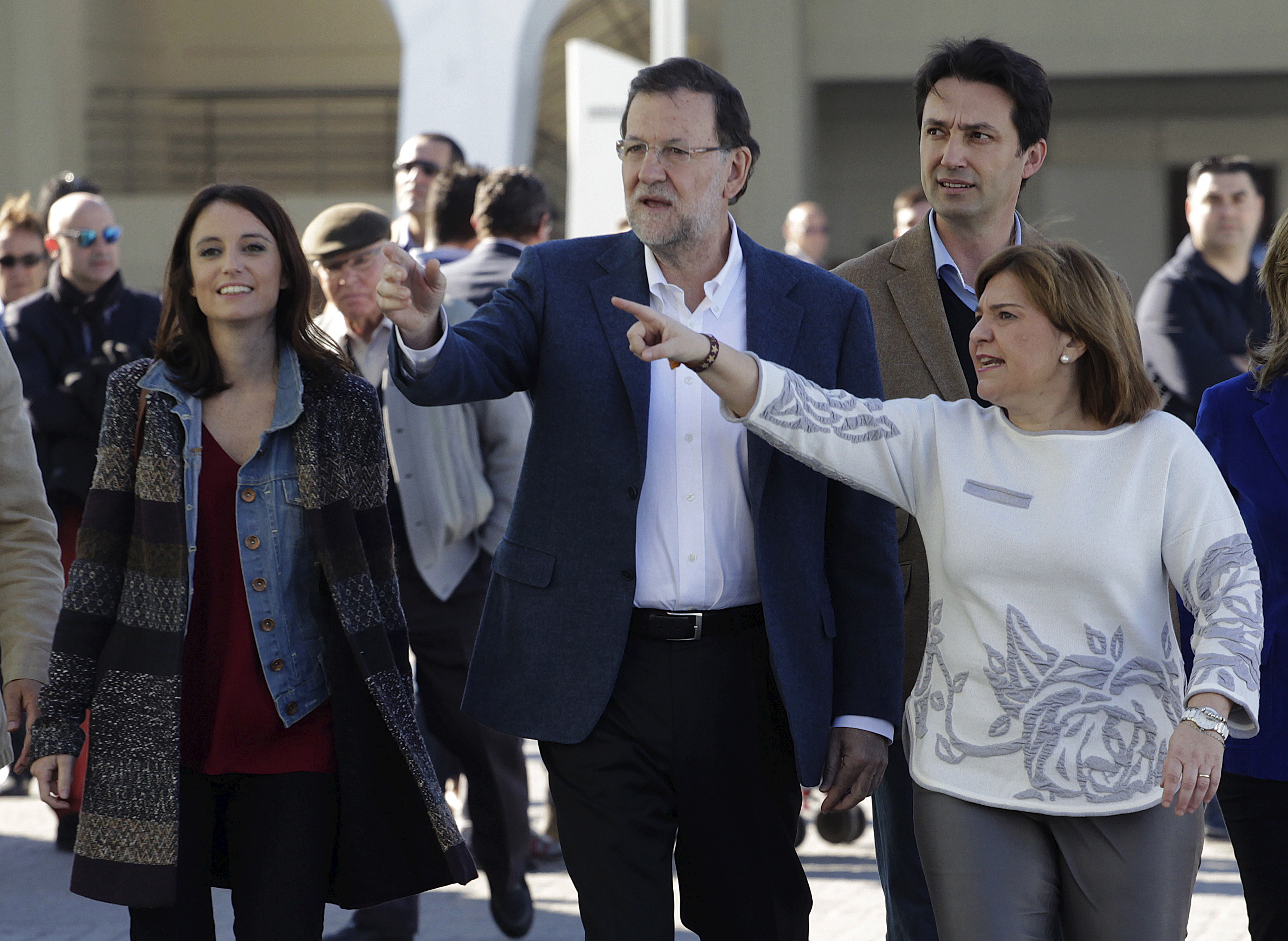Spain's Prime Minister Mariano Rajoy (C) gestures next to regional president Isabel Bonig (R) as he arrives at a meeting with People Party's candidates for parliament and supporters ahead the upcoming general elections next month in Valencia, Spain, November 28, 2015. REUTERS/Heino Kalis - RTX1W7Z9