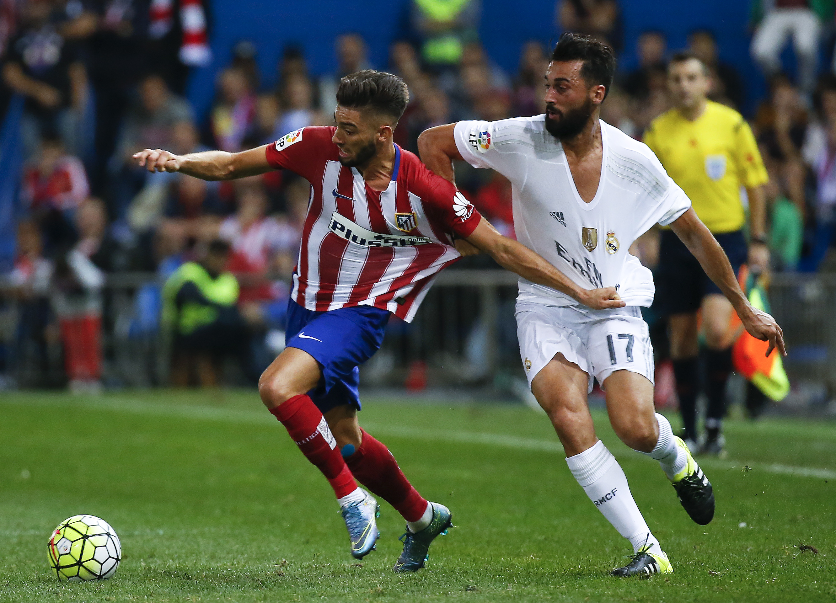 Atletico Madrid's Yannick Carrasco (L) is challenged by  Real Madrid's Alvaro Arbeloa during their Spanish first division derby soccer match at the Vicente Calderon stadium in Madrid, Spain, October 4, 2015.   REUTERS/Andrea Comas  - RTS30DF
