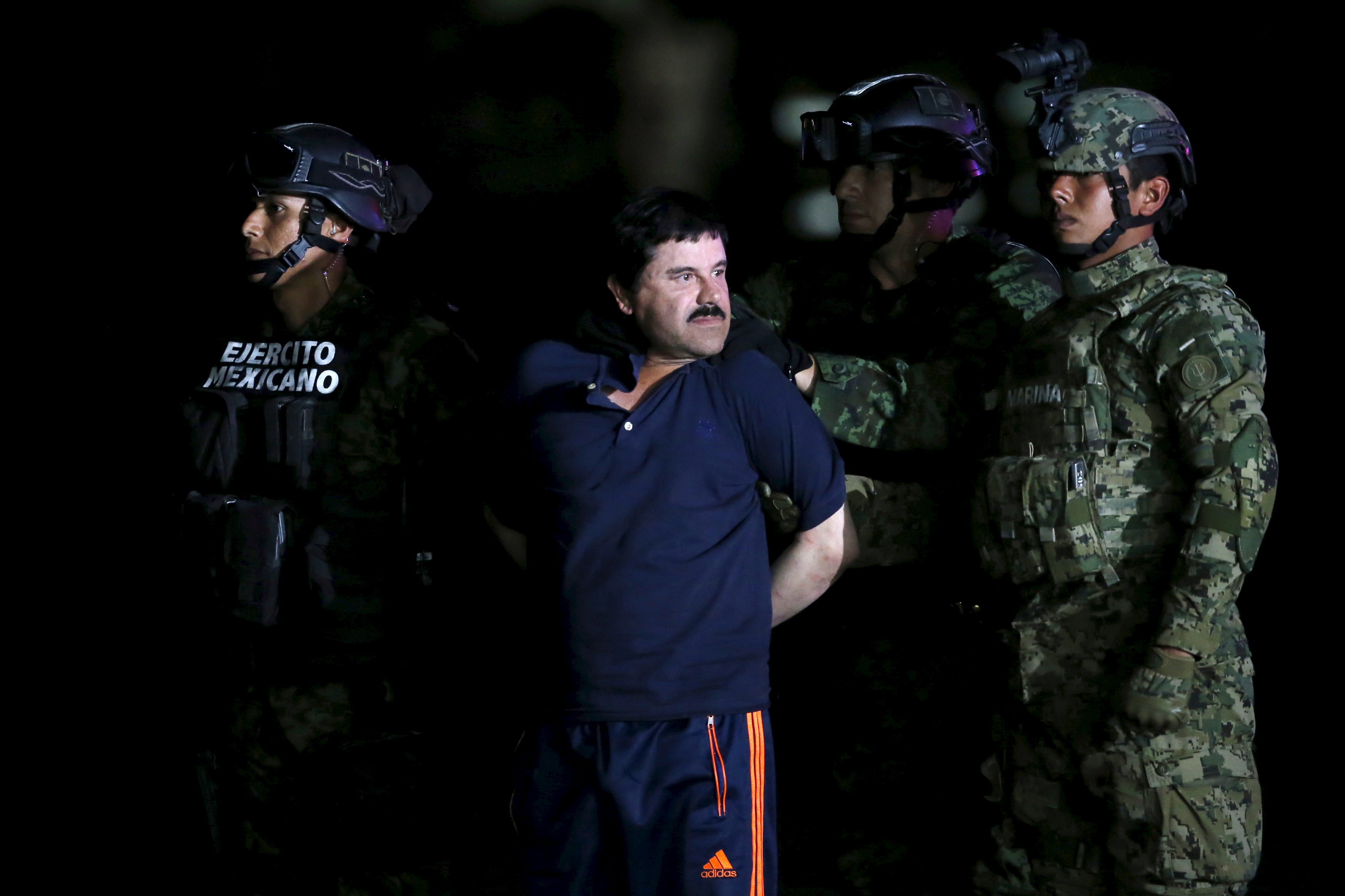 """Joaquin """"El Chapo"""" Guzman is escorted by soldiers during a presentation at the hangar belonging to the office of the Attorney General in Mexico City, Mexico January 8, 2016.  REUTERS/Edgard Garrido      TPX IMAGES OF THE DAY      - RTX21LRW"""