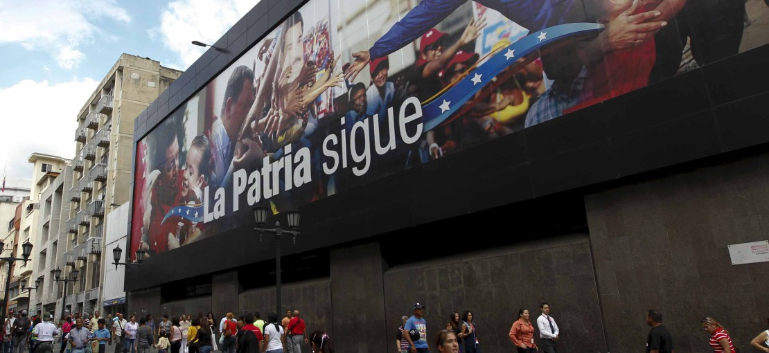 "People walk past a billboard depicting Venezuela's President Nicolas Maduro and Venezuela's late President Hugo Chavez and the words ""The country continues"" in Caracas December 10, 2015. REUTERS/Christian Veron - RTX1Y5T5"