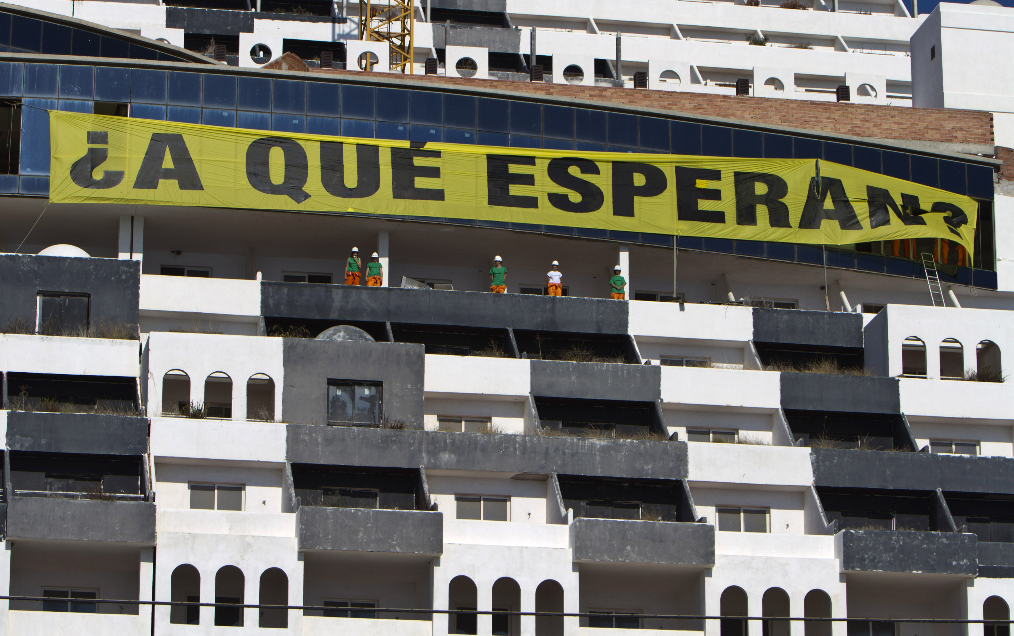 "Greenpeace activists stand under a banner reading ""What are they waiting for?"" in reference to the demolition of a hotel, after they occupied the construction site in El Algarrobico beach in Carboneras, southeastern Spain, September 5, 2011. Greenpeace say the construction of the hotel was ruled illegal due to a coastal protection law and Greenpeace members occupied an area of the construction site to demand the local government the immediate demolition of the building. REUTERS/Francisco Bonilla (SPAIN - Tags: ENVIRONMENT CIVIL UNREST BUSINESS CONSTRUCTION) - RTR2QTM7"