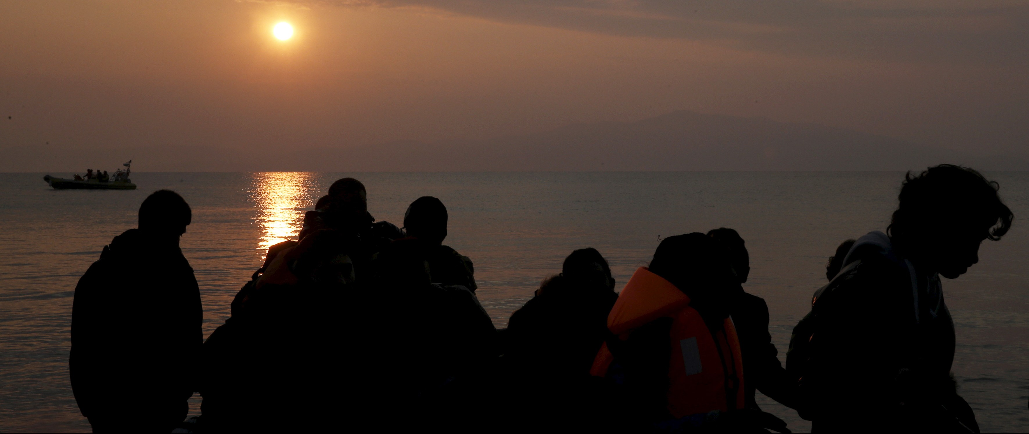 Refugees are silhouetted as they reach the shores of the Greek island of Lesbos on a dinghy during sunrise, March 20, 2016. REUTERS/Alkis Konstantinidis - RTSBA5L