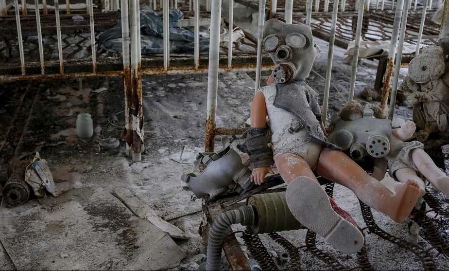 A doll in a children's gas mask is seen amongst beds at a kindergarten in the abandoned city of Pripyat near the Chernobyl nuclear power plant in Ukraine March 28, 2016.  REUTERS/Gleb Garanich - RTSCKBX