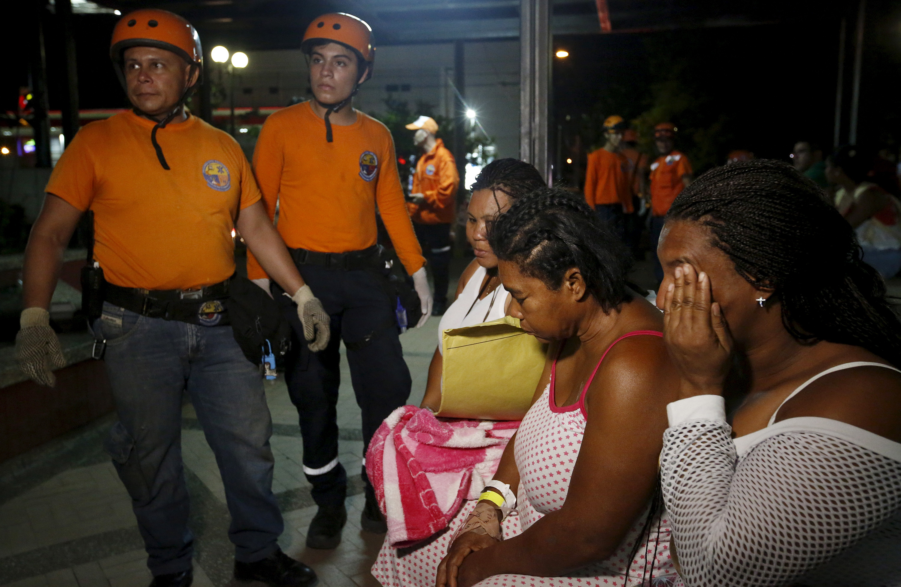 Rescue team members and patients react outside a clinic that was evacuated after tremors were felt resulting from an earthquake in Ecuador, in Cali, Colombia, April 16, 2016. REUTERS/Jaime Saldarriaga - RTX2AA56