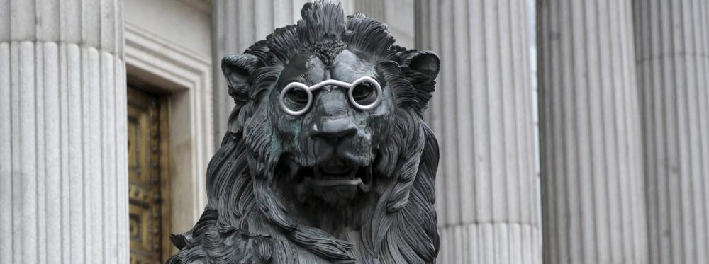"""A lion statue outside Spain's parliament in Madrid, Spain, is seen fitted with glasses to celebrate Spanish writer Miguel de Cervantes' famous novel """"Don Quijote"""" (Don Quixote), as part of a commemoration of the 400th anniversary of the writer's death, April 19, 2016. REUTERS/Andrea Comas - RTX2AMTF"""