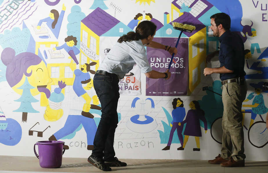 Podemos (We Can) leader Pablo Iglesias (L) and Izquierda Unida (United Left) leader Alberto Garzon, now running together in the coalition of Unidos Podemos (United We Can), put up an election campaign poster during an event to kick off the official campaign period for Spain's general election in Madrid, Spain, June 10, 2016.  REUTERS/Andrea Comas - RTSGTND