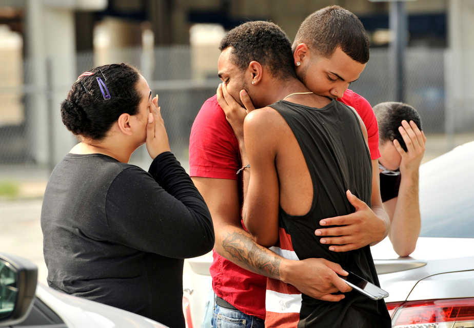 Friends and family members embrace outside the Orlando Police Headquarters during the investigation of a shooting at the Pulse night club, where as many as 20 people have been injured after a gunman opened fire, in Orlando, Florida, U.S June 12, 2016.  REUTERS/Steve Nesius     TPX IMAGES OF THE DAY      - RTX2FRIO