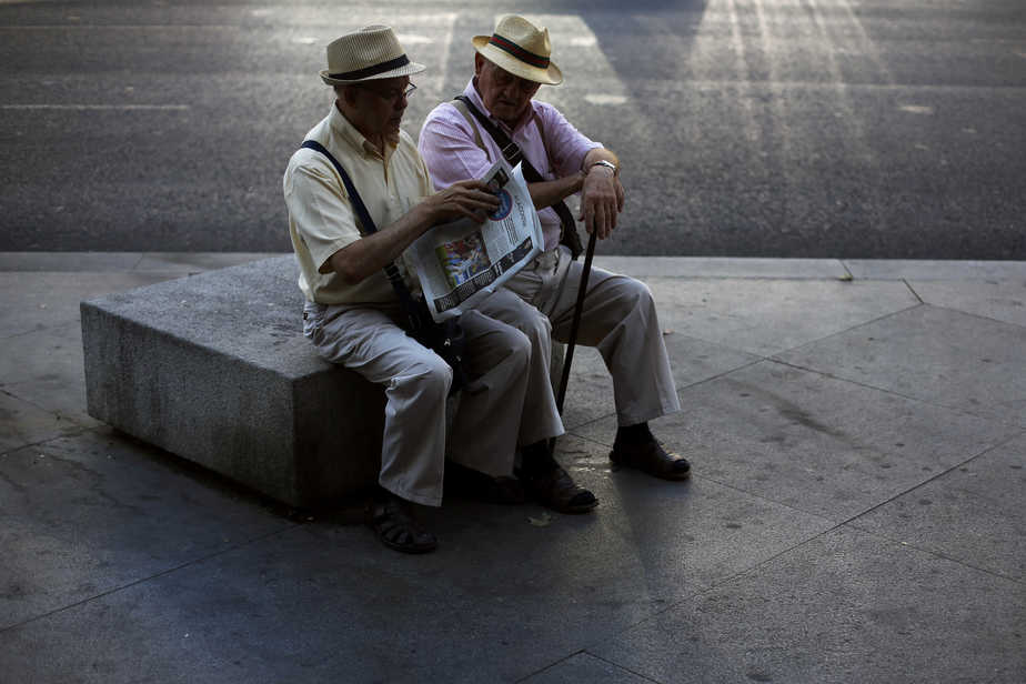 Two elderly men read the paper together in central Madrid September 9, 2014. REUTERS/Susana Vera (SPAIN - Tags: SOCIETY) - RTR45IFX