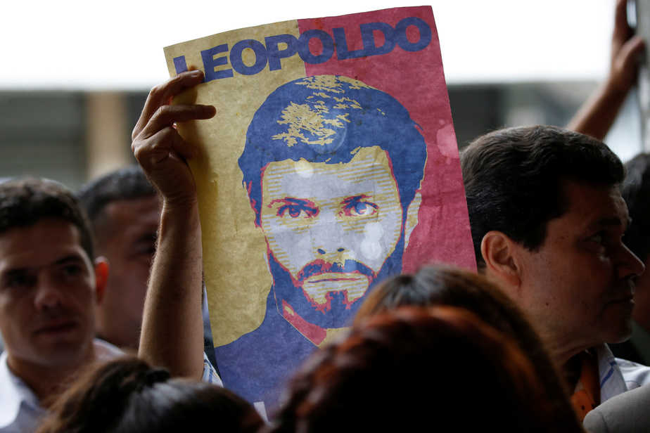 A supporter of jailed Venezuelan opposition leader Leopoldo Lopez holds a poster depicting him outside the courthouse in Caracas, Venezuela June 20, 2016. REUTERS/Carlos Garcia Rawlins - RTX2H7IN
