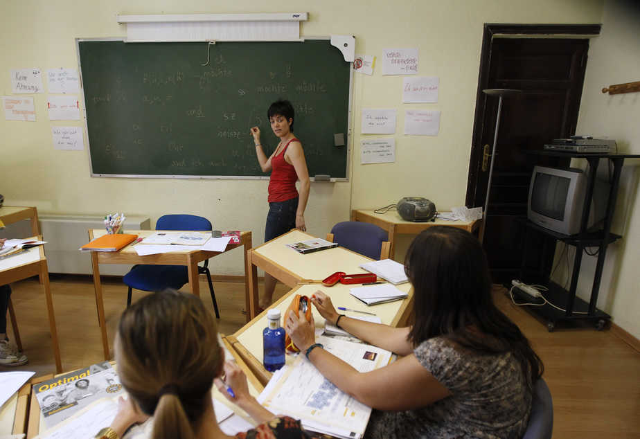 A teacher speaks to Spanish students during a German language class at an academy in Madrid May 18, 2012. A European Union survey in 2005 found the majority of Spaniards had not learned a second language: even those who wanted to improve their language skills did not make German their top choice, but preferred English and French. After France and the United Kingdom, Germany was the third most popular destination in Europe for Spanish migrants in 2011. Picture taken May 18, 2012.   To match Insight EUROPE/LABOUR        REUTERS/Andrea Comas (SPAIN - Tags: EDUCATION SOCIETY) - RTR32V5M