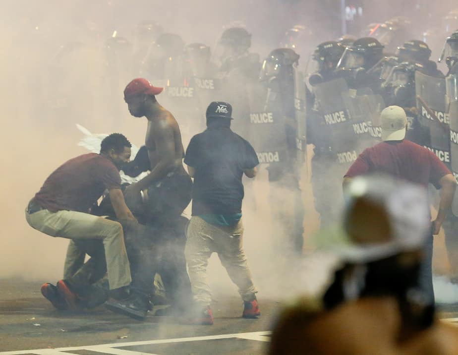 People maneuver amongst tear gas in uptown Charlotte, NC during a protest of the police shooting of Keith Scott, in Charlotte, North Carolina, U.S. September 21, 2016. REUTERS/Jason Miczek     TPX IMAGES OF THE DAY      - RTSOVKR
