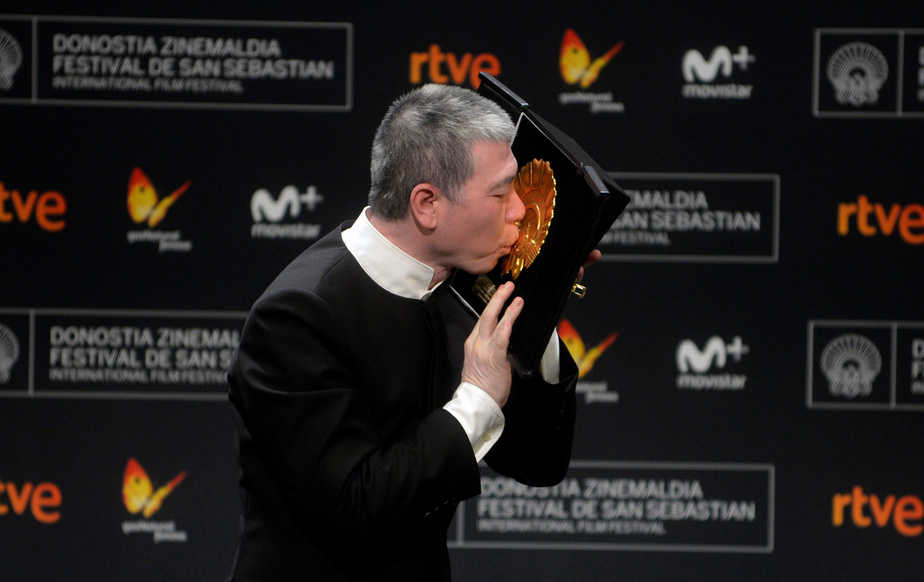 Director Feng Xiaogang kisses his Concha de Oro (Golden Shell) award for best film for the feature film I Am Not Madame Bovary during the awards ceremony at the San Sebastian Film Festival, September 24, 2016, in San Sebastian, northern Spain. REUTERS/Vincent West  - RTSPAC0