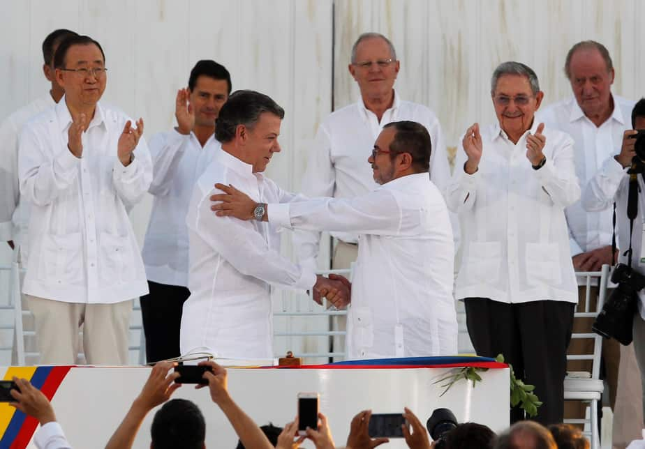 Colombian President Juan Manuel Santos (L) and Marxist rebel leader Timochenko shake hands after signing an accord ending a half-century war that killed a quarter of a million people, in Cartagena, Colombia September 26, 2016. REUTERS/John Vizcaino     TPX IMAGES OF THE DAY      - RTSPJY2