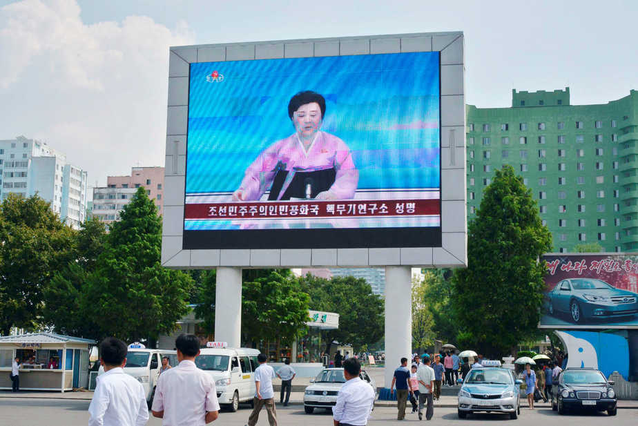 North Koreans walk past near a huge screen broadcasting the government's announcement on North Korea's fifth nuclear test in Pyongyang, North Korea, in this photo released by Kyodo September 9, 2016. Mandatory credit Kyodo/via REUTERS ATTENTION EDITORS - THIS IMAGE WAS PROVIDED BY A THIRD PARTY. EDITORIAL USE ONLY. MANDATORY CREDIT. JAPAN OUT. NO COMMERCIAL OR EDITORIAL SALES IN JAPAN. - RTX2ORUM