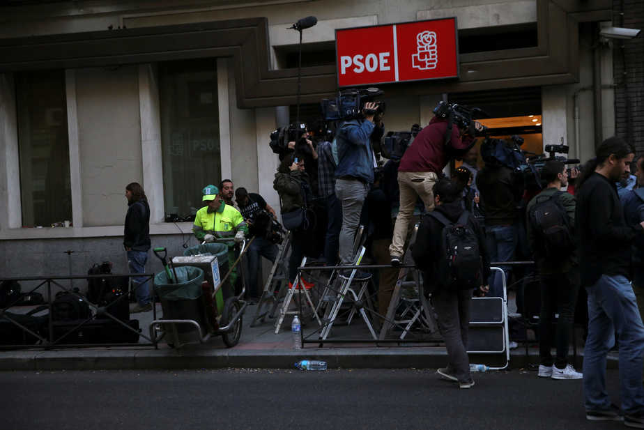 A municipal cleaner works next to the media as they stand outside the headquarters of Spain's Socialist party (PSOE) while waiting for the start of the party's assembly meeting in Madrid, Spain, October 1, 2016. REUTERS/Susana Vera - RTSQB55