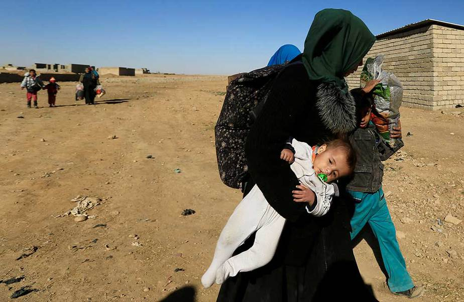 Una mujer desplazada y su hijo huyendo de los militantes islámicos en el barrio de Tahrir, se ven en Mosul, Irak el 22 de noviembre de 2016. REUTERS