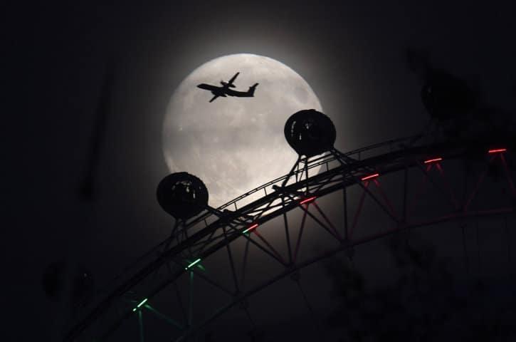 """Un avión vuela más allá de la rueda del ojo de Londres, y la luna, un día antes del espectáculo """"súper luna"""" en Londres, Gran Bretaña. REUTERS /"""