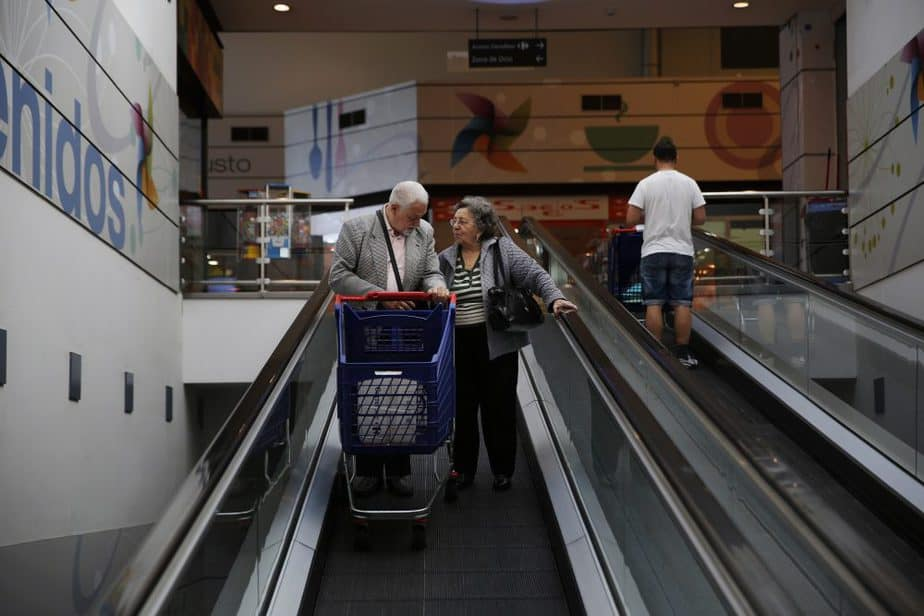 Angel Gomez Gamallo, 79, and his wife Luisa Fernandez Medarde, 81, leave a supermarket with a box full of food destined for one of their four children in Madrid April 29, 2014. When they retired a decade ago, Gomez and his wife had imagined spending their 3,600 euros in joint pension payments only on restaurants, holidays and toys for the grandkids. Today, their retirement money also helps support five families. The Spanish couple, like other relatively prosperous pensioners across southern Europe, are providing an informal safety net which has helped many in the younger generation to avoid widespread poverty despite record-high unemployment. Picture taken April 29, 2014. To match Insight story EUROPE-SOUTH/PENSIONS        REUTERS/Susana Vera (SPAIN - Tags: BUSINESS EMPLOYMENT POLITICS SOCIETY) - RTR3R5MA