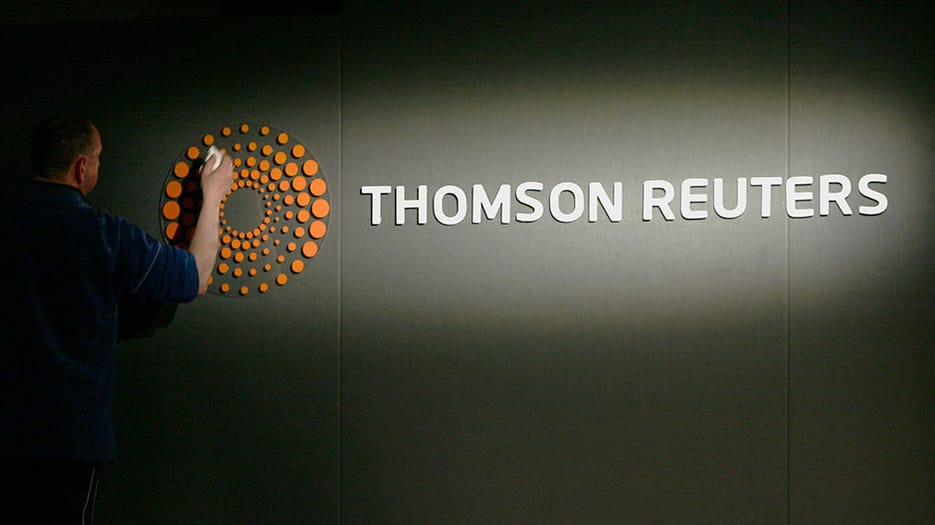A man polishes a new logo of Thomson Reuters at the Reuters head offices at Canary Wharf in London April 16, 2008.