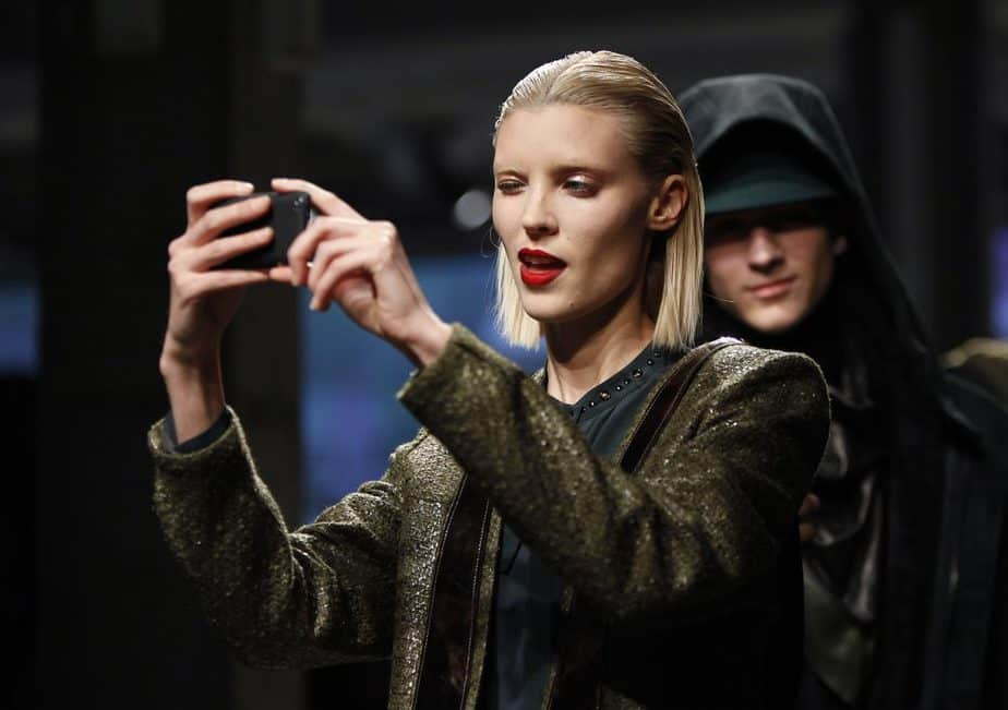 A model takes a photo with a smart phone as she presents a creation from the Kenneth Cole Autumn/Winter 2013 collection during New York Fashion Week in New York, February 7, 2013. REUTERS/Carlo Allegri  (UNITED STATES - Tags: FASHION) - RTR3DHHH