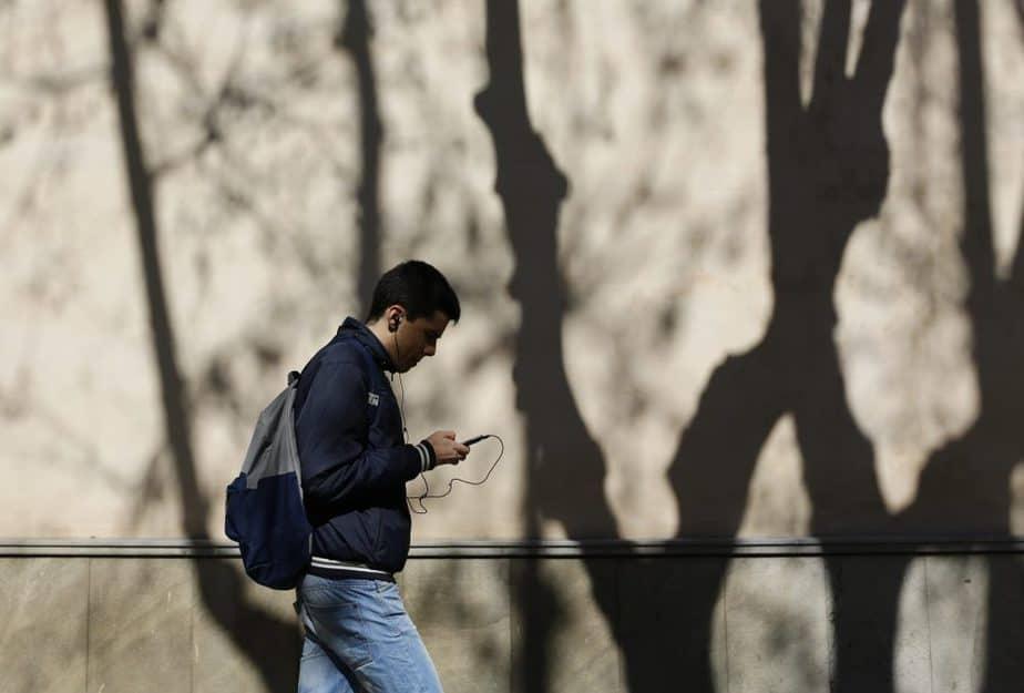 Un hombre camina con su teléfono móvil. FOTO: Reuters