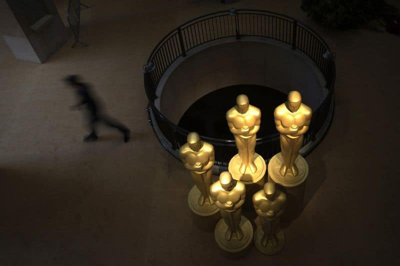 A man walks past large Oscar statues placed outside the entrance to the Dolby Theatre, the site for the 85th Academy Awards in Los Angeles, California, February 23, 2013. The Oscars will be presented on February 24, 2013.  REUTERS/Adrees Latif  (UNITED STATES - Tags: ENTERTAINMENT)