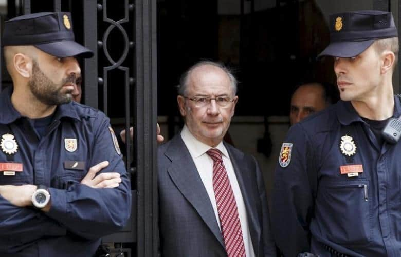 Former International Monetary Fund chief Rodrigo Rato (C) walks between police officers as he leaves his office in Madrid April 17, 2015.   REUTERS/Andrea Comas