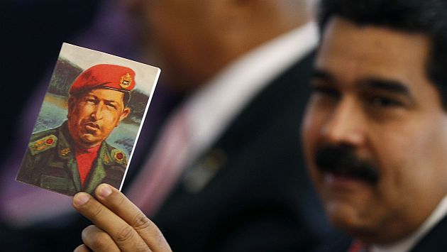 Venezuela's President Nicolas Maduro holds a photo of former Venezuelan President Hugo Chavez during the meeting of China and CELAC at Itamaraty Palace in Brasilia July 17, 2014. Brazil hosted the meeting of China and Community of Latin American and Caribbean States (CELAC). REUTERS/Ueslei Marcelino (BRAZIL - Tags: POLITICS)