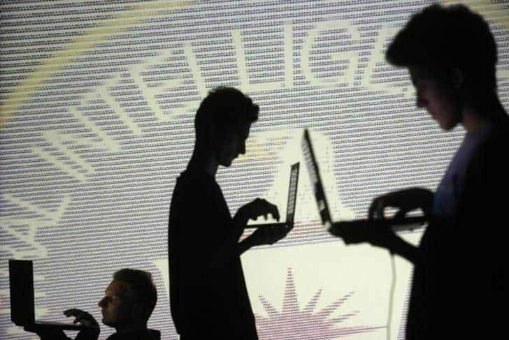 People are silhouetted as they pose with laptops in front of a screen projected with binary code and a Central Inteligence Agency (CIA) emblem, in this picture illustration taken in Zenica October 29, 2014. REUTERS/Dado Ruvic