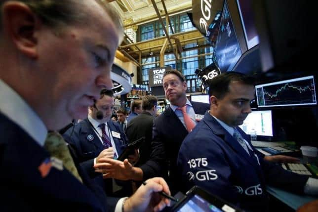Traders work on the floor of the New York Stock Exchange (NYSE) as the Dow Jones Industrial Average passes the 20,000 mark shortly after the opening of the trading session in New York, U.S., January 25, 2017. REUTERS/Brendan McDermid