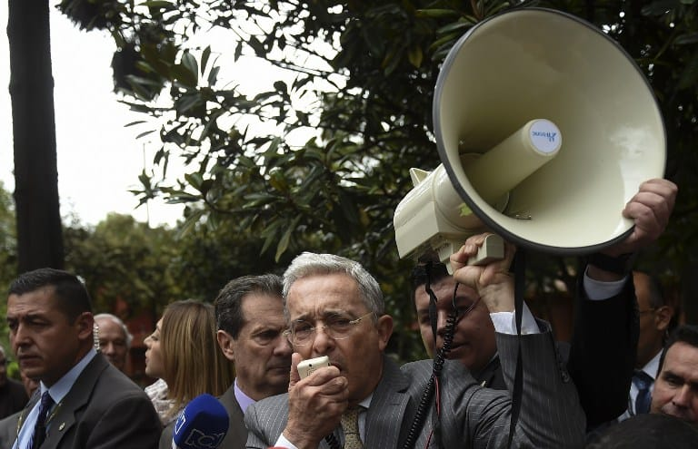 Former Colombian president (2002-2010) and current senator Alvaro Uribe (C) takes part in a  protest against the government of Venezuelan President Nicolas Maduro, in Bogota, Colombia, on April 19, 2017.  Clashes broke out Wednesday in Venezuela at massive protests against Maduro, as riot police fired tear gas to push back stone-throwing demonstrators and a young protester was shot dead. Violence erupted when thousands of opposition protesters tried to march on central Caracas, a pro-government bastion where red-clad Maduro supporters were massing for a counter-demonstration. / AFP PHOTO / RAUL ARBOLEDA