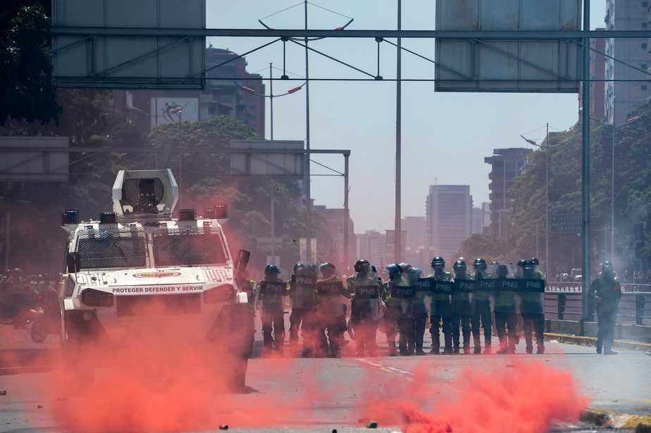 "Riot police clash with demonstrators protesting against President Nicolas Maduro's government in Caracas on April 8, 2017.  The opposition is accusing pro-Maduro Supreme Court judges of attempting an internal ""coup d'etat"" for attempting to take over the opposition-majority legislature's powers last week. The socialist president's supporters held counter-demonstrations on Thursday, condemning Maduro's opponents as ""imperialists"" plotting with the United States to oust him.  / AFP PHOTO / FEDERICO PARRA"