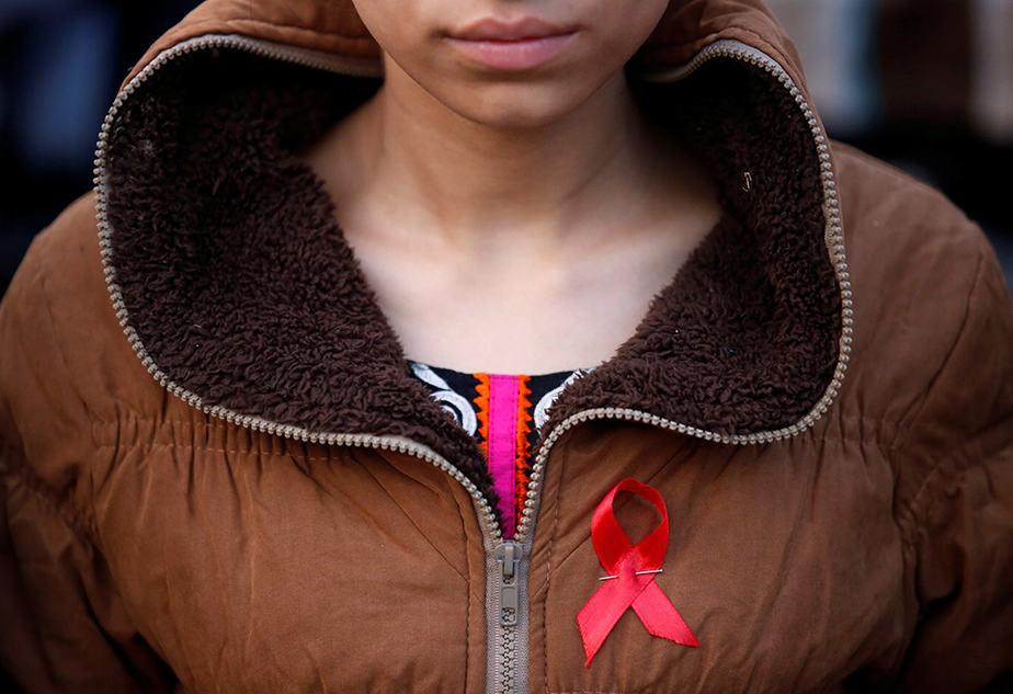 Persona con un lazo contra el sida. FOTO: Reuters