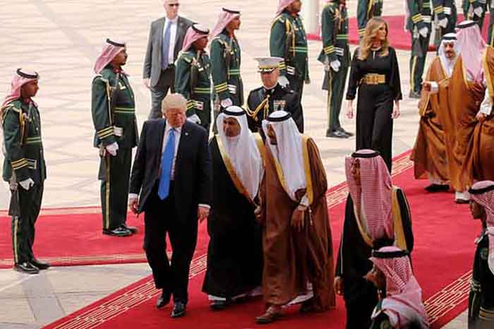 Saudi Arabia's King Salman bin Abdulaziz Al Saud (C, in brown and white) welcomes U.S. President Donald Trump (L) and first lady Melania Trump (top, 3-R) with a military honor cordon after they arrived aboard Air Force One at King Khalid International Airport in Riyadh, Saudi Arabia May 20, 2017. REUTERS/Jonathan Ernst - RTX36OSG