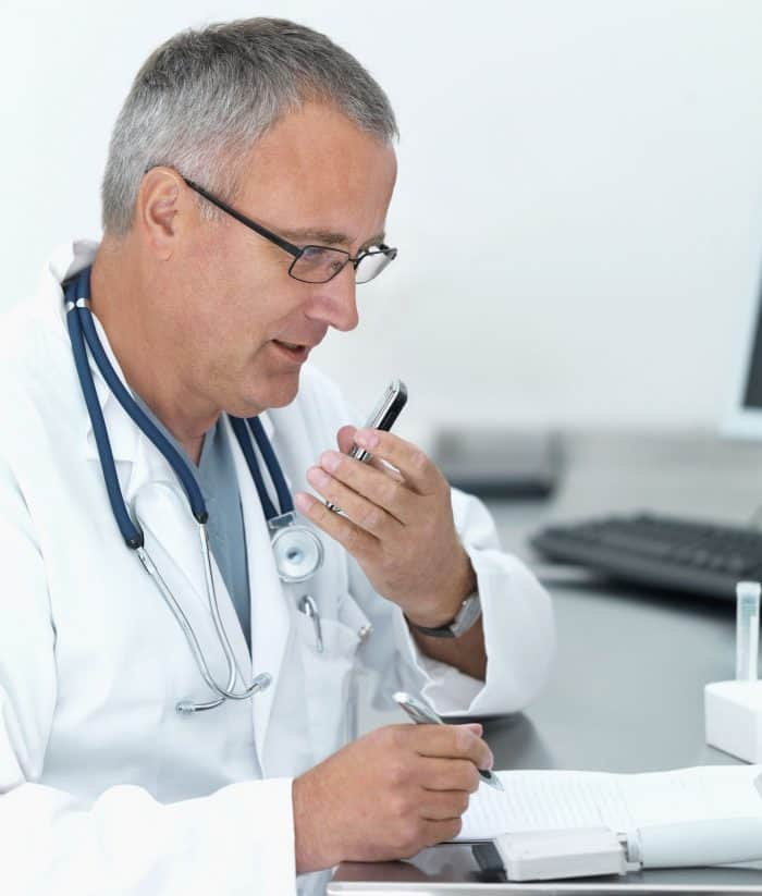 Mature doctor recording notes with his cellphone
