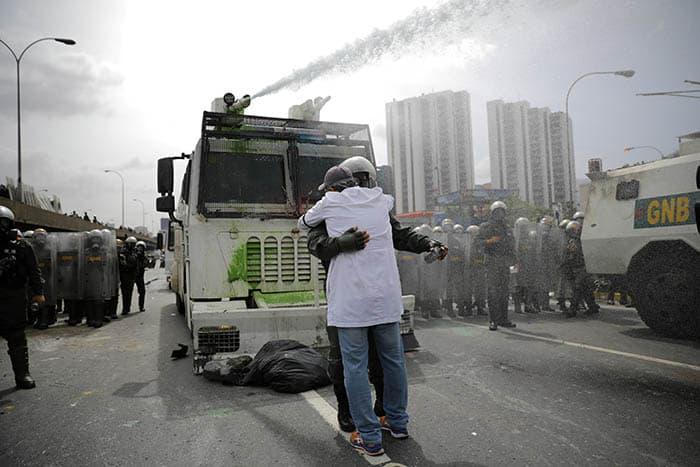 Abrazo entre un manifestante y un policía en Caracas, Venezuela. FOTO: Reuters
