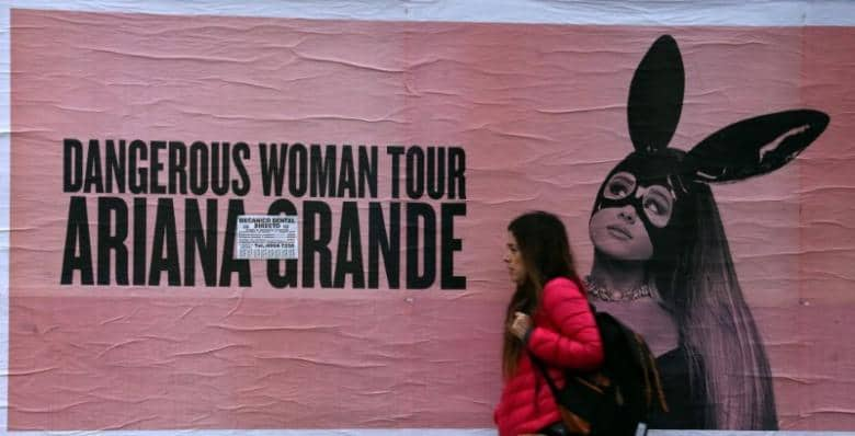A woman walks past a billboard advertising U.S. singer Ariana Grande's world tour in Buenos Aires, Argentina May 24, 2017. REUTERS/Marcos Brindicci