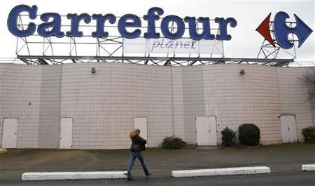 A woman walks below the logo of Carrefour Planet supermarket in Bordeaux, southwestern France, January 19, 2012. REUTERS/Regis Duvignau
