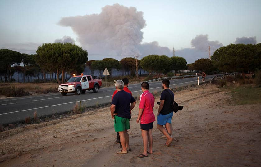 Varias personas observan el fuego avivado en el entorno del Parque Nacional de Doñana. FOTO: Reuters