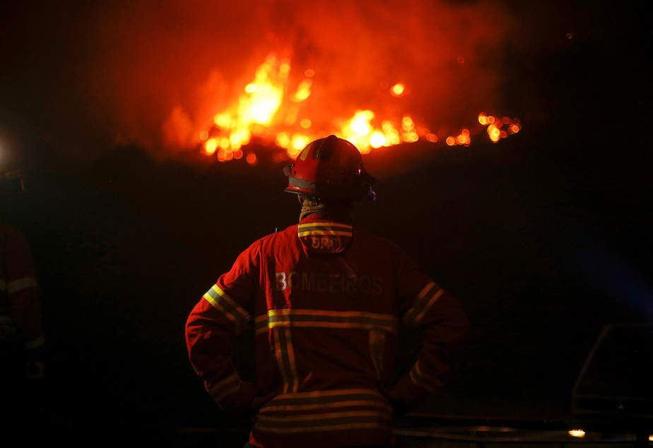 Un bombero mira un incendio forestal que se acerca en Carvalho, cerca de Gois, Portugal,