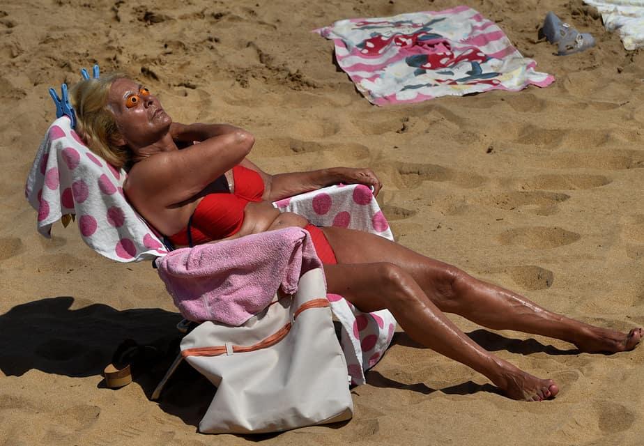 Una mujer toma el sol en la playa de San Lorenzo durante una ola de calor en Gijón