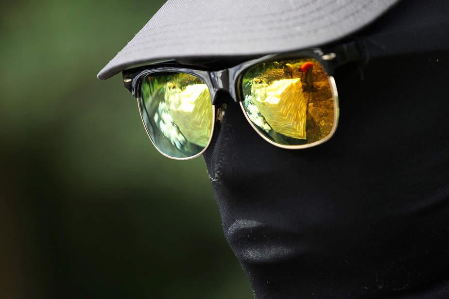 Un soldado está de guardia cuando los trabajadores que mueven paquetes que contienen cocaína y otras sustancias para la incineración se reflejan en sus gafas de sol, en una base militar en Santo Domingo