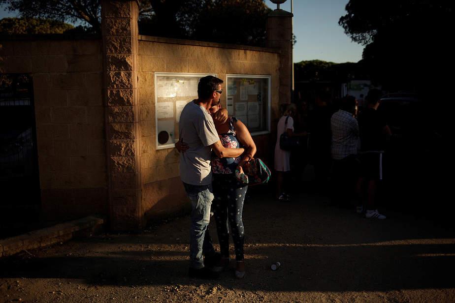 Una mujer llora mientras es abrazada por su esposo después de que su caravana y sus pertenencias fueron quemadas en la entrada a un área de camping quemada después de un incendio forestal cerca del Parque Nacional Donana, en Matalascanas