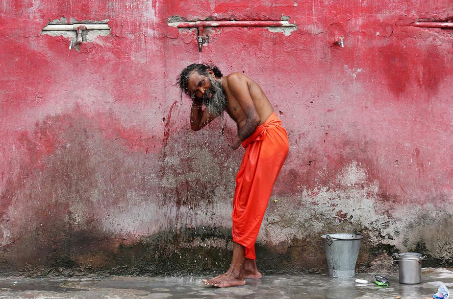 Un sadhu o un hombre santo hindú se baña antes de registrarse para la peregrinación anual al santuario de la cueva de Amarnath, en un campamento base en Jammu